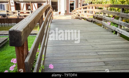 Beautiful toned image of small wooden bridge across river in european town at bright sunny day - Stock Photo