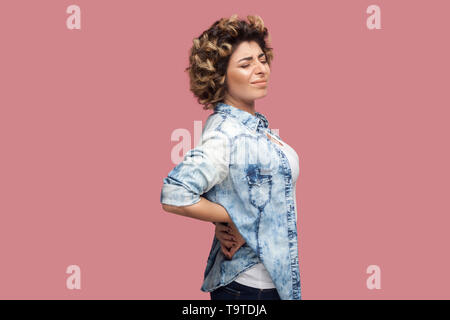 Back, kidney or spine pain. Profile side view portrait of sad young woman with curly hairstyle in casual blue shirt standing and endure pain on back.  - Stock Photo