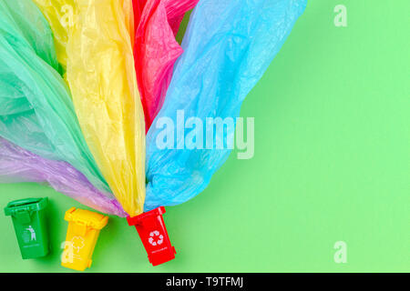 Recycling garbage background. Colorful recycle bins containers with single use plastic bags - Stock Photo