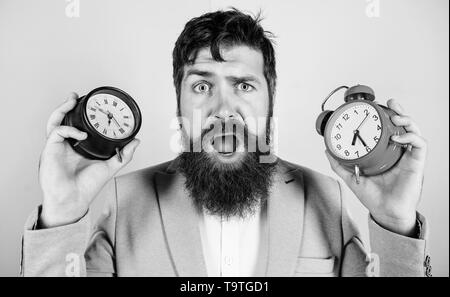 Does changing clock mess with your health. Man bearded hipster hold two different clocks. Guy unshaven puzzled face having problems with changing time - Stock Photo