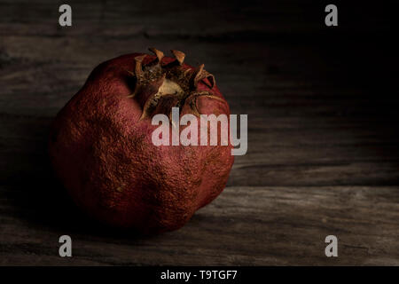 aged pomegranate on wooden background - Stock Photo