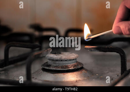 Dirty gas hob being lit with a match - Stock Photo