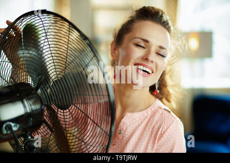 smiling modern housewife in the modern living room in sunny hot summer day enjoying breeze air in the front of working fan. - Stock Photo