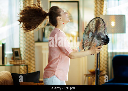 smiling modern housewife in the modern living room in sunny hot summer day enjoying fresh air in the front of working fan. - Stock Photo
