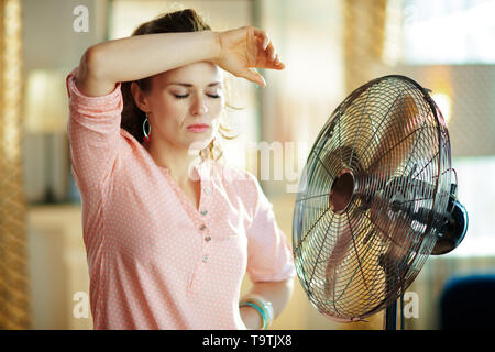 sad stylish housewife in the modern living room in sunny hot summer day exhausted from summer heat while standing in the front of fan. - Stock Photo