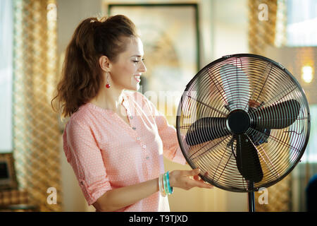 smiling stylish housewife in the modern living room in sunny hot summer day near electric metallic fan. - Stock Photo