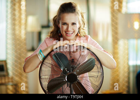 Portrait of smiling young housewife with electric metallic fan in the modern house in sunny hot summer day. - Stock Photo