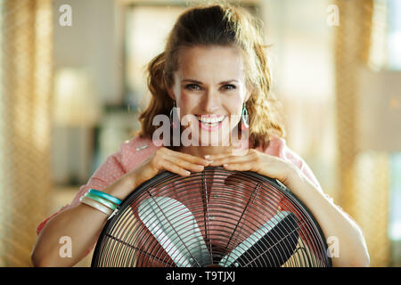 Portrait of smiling stylish housewife with metallic floor standing fan in the modern living room in sunny hot summer day. - Stock Photo