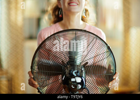 Closeup on smiling young housewife in the modern living room in sunny hot summer day cooling down in the front of working fan. - Stock Photo