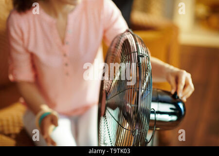 Closeup on young housewife in the modern house in sunny hot summer day swtitching on metallic floor standing fan. - Stock Photo