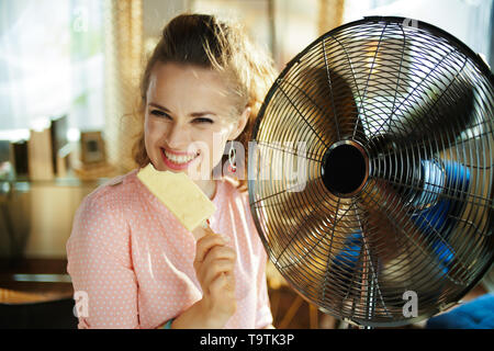 happy stylish woman with ice cream cooling down using electric metallic fan in the modern house in sunny hot summer day. - Stock Photo
