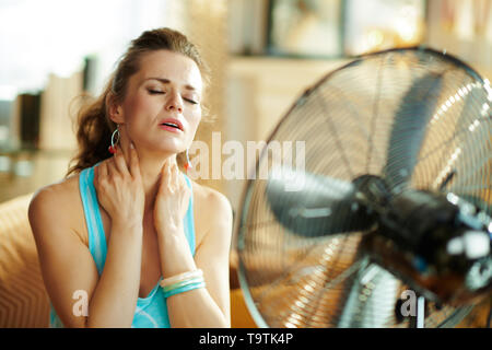 relaxed young woman in the modern living room in sunny hot summer day cooling down in the front of fan suffering from summer heat. - Stock Photo