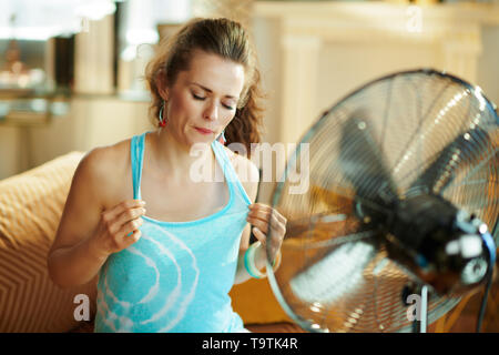 sweating woman at modern home in sunny hot summer day cooling down using electric floor standing fan suffering from summer heat. - Stock Photo