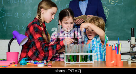 back to school. kids in lab coat learning chemistry in school laboratory. chemistry lab. making experiment in lab or chemical cabinet. happy children  - Stock Photo