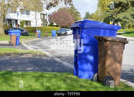 Recycle bins and compost bins line a street awaiting collection from the city - Stock Photo