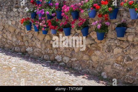 Rock wall full of attached blue flower pots. Typical andalusian architecture background - Stock Photo