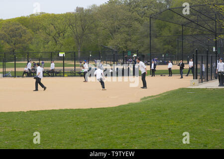 Orthodox Jewish boys play baseball in Prospect Park wearing their recognizable uniforms of black pants and white shirts. Brooklyn, New York. - Stock Photo