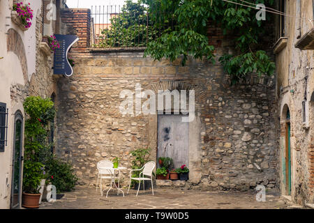 A small square in the middle of Benevento invites to sit down and enjoy a peaceful moment. A sign says 'Bed & Breakfast Le Streghe ('the witches'). - Stock Photo