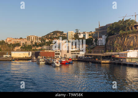 Portugal, Funchal - July 31, 2018: View of the port of the city from the departing ship in the early morning. - Stock Photo