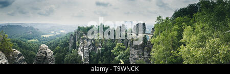 Beautiful panoramic view of famous Bastei Bridge with Elbe Sandstone mountains in Saxon Switzerland National Park on a moody day, Saxony, Germany - Stock Photo