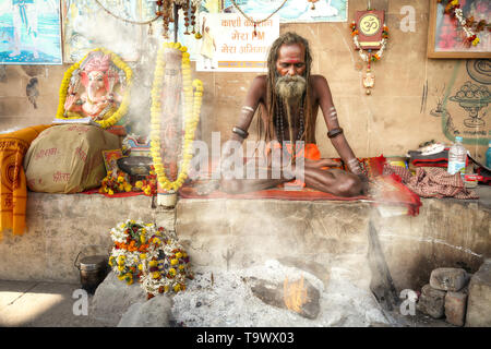 Sadhu baba at Varanasi sitting in meditation posture with holy fire burning at the Ganges river ghat - Stock Photo