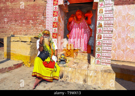 Indian Sadhu baba sitting in front of a Hanuman temple at Varanasi Ganges river ghat - Stock Photo