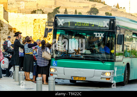 Jerusalem, Israel- August 17, 2016: Group of orthodox Jews waiting to get on a public transit bus at the Dung Gate bus stop in Old City of Jerusalem - Stock Photo