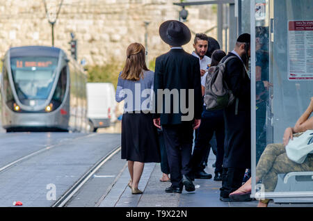 Jerusalem,Israel- August 17, 2016: Jewish Orthodox man and woman waiting for the train at City Hall stop near Jaffa Gate in the Old City of Jerusalem, - Stock Photo