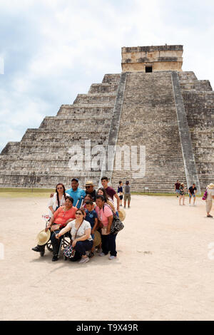 Mexico tourists taking a group selfie; Temple of Kukulcan ( El Castillo ), Chichen Itza Mayan Ruins, Yucatan, Mexico. Example of Mexico travel. - Stock Photo