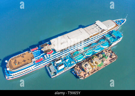 Refueling at sea - Small Oil products ship fuelling a large Bulk carrier, aerial image. - Stock Photo