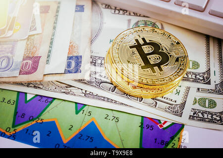 Golden bitcoin coin on placed on multiple banknotes and graphs on paper showing exchange rates between cryptocurrency and real money - Stock Photo