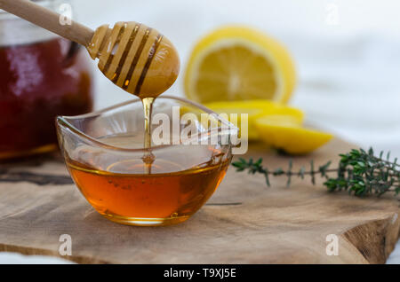 Honey in jar with honey dipper,  thyme and lemon on wooden background - Stock Photo