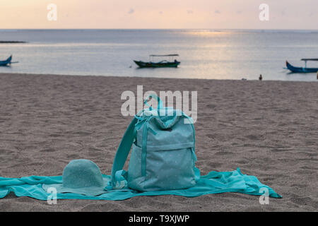 Bright backpack, pareo and hat lie on the sandy beach. Summer travel concept, With copy space for text - Stock Photo