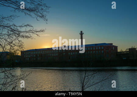 Beautiful sunset on the Knazal lake on the background of a large old weaving factory, the city of Yuzha, Ivanovo region, Russia. - Stock Photo
