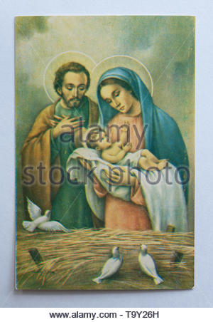 Vintage antique Catholic image of Joseph and Mary holding baby Jesus. The child is shown with blond hair. There are straw and doves in the bottom of t - Stock Photo