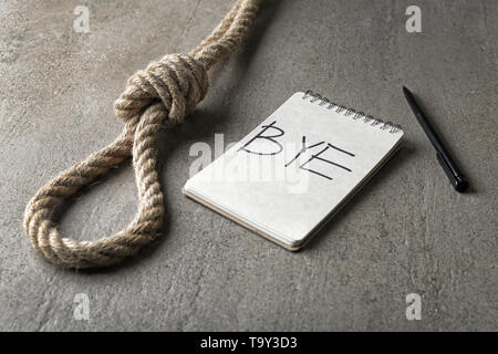 Rope with loop, text BYE in notebook and pen on grey background. Suicide concept - Stock Photo