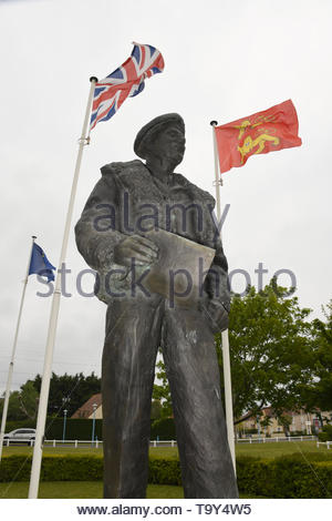 Statue of Monty - General Montgomery in Colleville-Montgomery, Normandy in France with flags flying. Flag of Normandy, French and Union Jack - Stock Photo