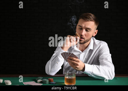 Young man playing poker in casino - Stock Photo