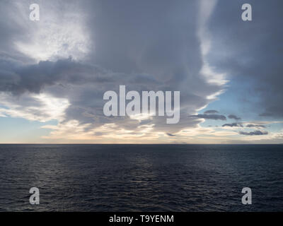 The Atlantic Ocean at South Georgia with dramatic clouds at sunrise. - Stock Photo