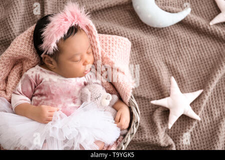 Cute African-American baby sleeping in wicker basket on color plaid - Stock Photo