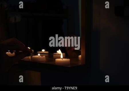 Woman lighting candles on shelf in dark room - Stock Photo