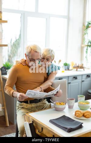 Loving wife tenderly hugging a spouse during newspaper reading - Stock Photo