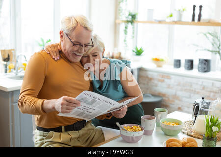 smiling nice appealing aged white haired married couple reading a newspaper together t9ywg3