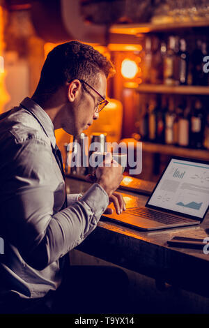 Freelancer drinking coffee and working sitting in his restaurant