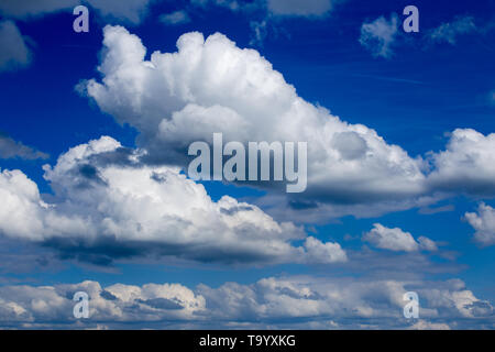Regular spring clouds on blue sky at daylight in continental europe. Shot wit telehoto lens and circular polarizing filter. - Stock Photo
