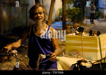Cute old man with beard and white hair transport two dog on styrofoam box behind motorbike to get vaccine at night, he stop under yellow street lamp - Stock Photo