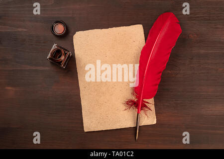 A vintage background with a quill pen on a piece of old parchment paper, with an ink well, shot from the top on a dark wooden background - Stock Photo