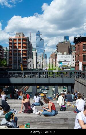 People relaxing at the high line, urban park redeveloped from an abandoned elevated rail line in Chelsea, Manhattan New york city, NY / USA - Stock Photo
