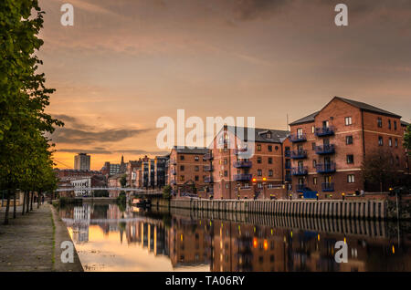 Brick apartment buildings and renovated warehouses along the river Aire in Leeds at Sunset. Reflection in water. - Stock Photo