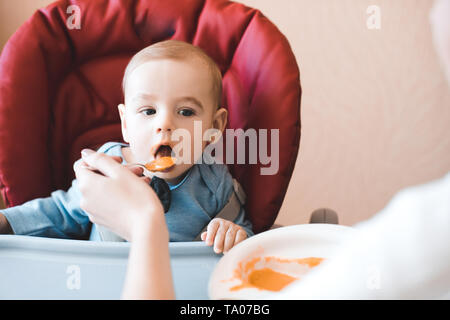 Baby boy 1 year old eating mashed apple sitting in chair in kitchen. Mother feeding child. Childhood. - Stock Photo